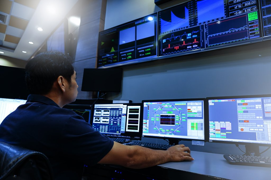 technicien en face de plusieurs écrans dans un bureau